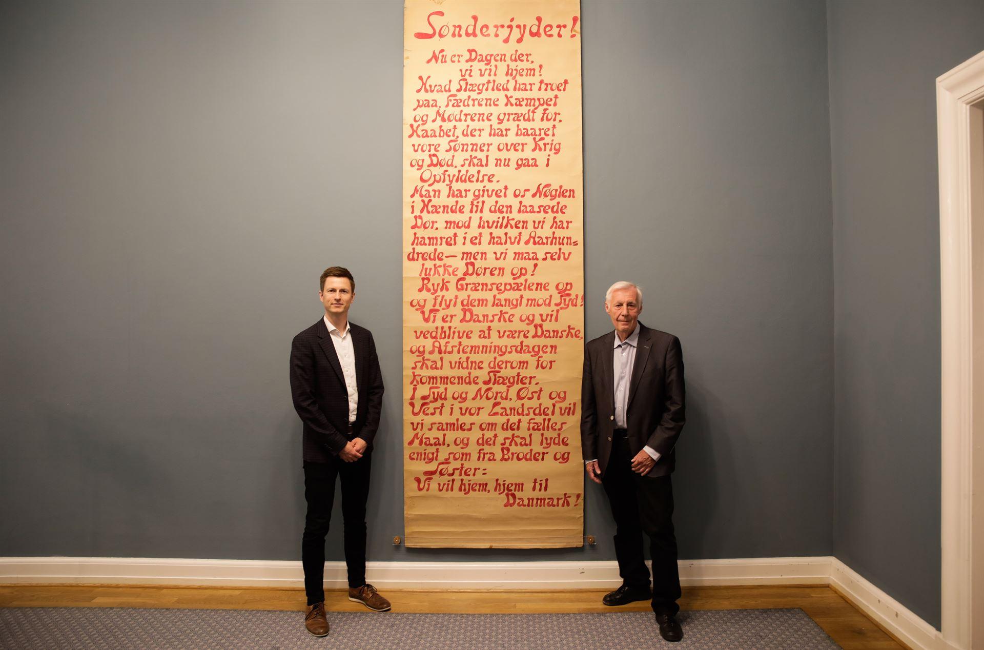 Jesper Petersen (t.v.) og Henrik Dam Kristensen ved den historiske afstemningsplakat. Foto: Pressefoto